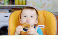 Funny baby boy eating round cracknel age of year on kitchen Royalty Free Stock Image