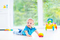 Funny baby boy playing with colorful ball and toy car
