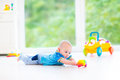 Funny baby boy playing with colorful ball and toy car Royalty Free Stock Photo