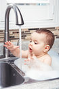 Funny baby girl boy with dark black eyes sitting in big kitchen sink with water and foam