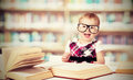 Funny baby girl in glasses reading book in library