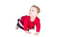 Funny baby girl in a red dress learning to crawl