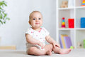 Funny baby kid girl sitting on floor in children room Royalty Free Stock Photo