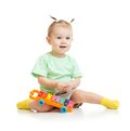 Funny baby playing with xylophone isolated Royalty Free Stock Photo