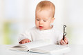 Funny baby reading a book with glasses Stock Image