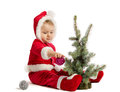 Funny baby in santa claus clothes is decorating xmas tree on white background Stock Images