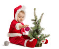 Funny baby in santa claus clothes is decorating xmas tree on white background Stock Image