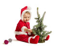 Funny baby in santa claus clothes is decorating xmas tree on white background Stock Photography