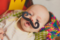 Funny baby trying paper mustache cute boy with photo props decorations crown Stock Photography