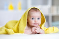 Funny baby under soft towel. Cute child lying on bed after bathing in living room Royalty Free Stock Photo