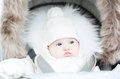 Funny baby in a warm stroller on a cold winter day Royalty Free Stock Photo