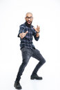 Funny baldheaded young african american man showing karate kick with beard standing and Royalty Free Stock Photo