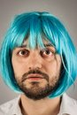 Funny bearded man blue wig grey background Stock Images
