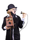 Funny bearded woman wide rimmed spectacles spectacles black homburg trilby hat jacket holding antique phone isolated white Royalty Free Stock Photo