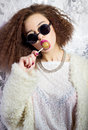 Funny beautiful girl in glasses and a white coat licks a candy bar, bright makeup, fashion photography Studio Royalty Free Stock Photo