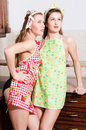 Funny beautiful young woman attractive pinup girl friends standing in aprons looking up at copy space two women Stock Image