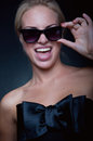 Funny blond wearing sun glasses beautiful young woman model stylish black top with big silk bow bright pink lipstick having fun Royalty Free Stock Photos