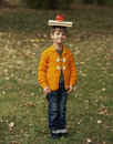 Funny boy with book on his head little and apple Stock Photography