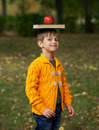 Funny boy with book on his head little and apple Royalty Free Stock Photo