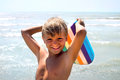 Funny boy joking with kickboard on seashore in a summer day Stock Photography