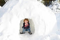 Funny boy in snow igloo on a sunny winter day Royalty Free Stock Photo