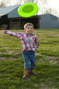 Funny boy throwing frisbee smiling on a farm Stock Photography