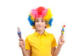 Funny boy wears colorful wig and holds a wooden clowns isolated on white background Royalty Free Stock Photography