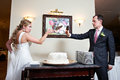 Funny bride and groom near wedding cake in interior Royalty Free Stock Photography