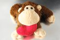 Funny brown monkey peluche and a red heart Stock Images