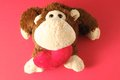 Funny brown monkey peluche and a red heart Royalty Free Stock Image