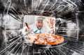Funny chef perplexed and angry loser is destiny overlooked pizza in the oven so she had scorched view from the inside of the oven Stock Photos