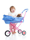 Funny child with attractive kitten in carriage toy Royalty Free Stock Photo