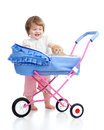 Funny child with attractive kitten in carriage toy Stock Photography