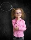 Funny child in eyeglasses standing near school chalkboard Royalty Free Stock Photo