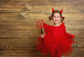 Funny child girl in devil halloween costume on dark wooden back
