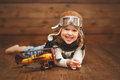 Funny child girl pilot aviator with airplane laughing Royalty Free Stock Photo