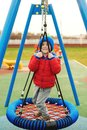 Funny child having fun with modern swing. Little boy playing on outdoor playground. Happy kid swinging on cold autumn day. Active Royalty Free Stock Photo