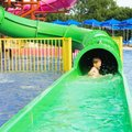 Funny child playing in water park splashing water. Summer holidays concept. Boy has into pool after going down water slide on sum Royalty Free Stock Photo