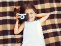Funny child shooting vintage old retro camera and having fun on the plaid top view Stock Photos