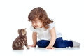 Funny child sitting on floor. Kitten looks at girl Royalty Free Stock Photography