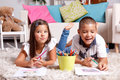 Funny children drawing at home brother and sister in the living room Stock Photos