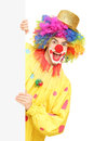 Funny circus clown holding a blank panel isolated on white background Royalty Free Stock Image