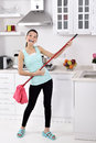 Funny cleaning woman in home after the beautiful young happy having fun by playing air guitar with the mop Stock Image