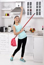 Funny cleaning woman in home after the beautiful young happy having fun by playing air guitar with the mop Stock Photography