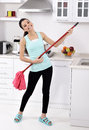 Funny cleaning woman in home after the beautiful young happy having fun by playing air guitar with the mop Royalty Free Stock Photography