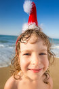 Funny closeup portrait of baby in santa hat child having fun at the tropical beach xmas holidays concept Royalty Free Stock Images