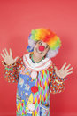 Funny clown with arms raised looking away against colored background Stock Photography