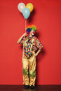 Funny clown with balloons on red background Stock Images