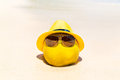 Funny coconut in sunglasses and yellow hat lies on a sandy tropical beach. Sea in the background . Summer vacation concept . Royalty Free Stock Photo