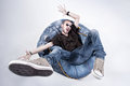 Funny crazy man dressed in jeans and sneakers standing on denim beanbag Royalty Free Stock Photography